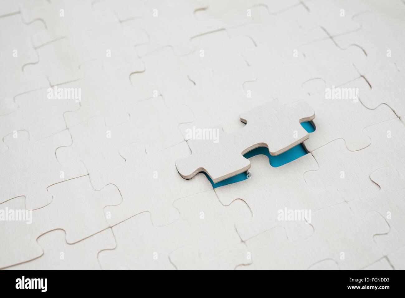 Puzzle con un pezzo sollevato su sfondo blu Immagini Stock