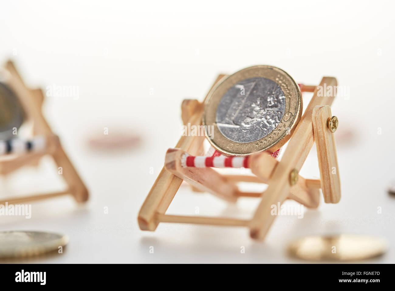 Concetto di pensione shot con euro moneta denaro in relax sulla sdraio in miniatura Immagini Stock