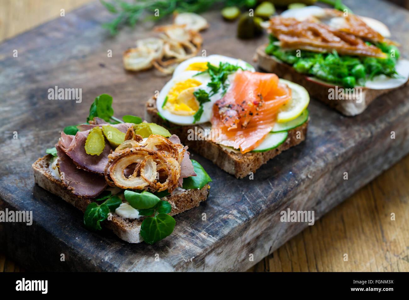 Scandinavian Open panini con sgombro affumicato, salmone e uova e roast beef e cipolla croccante Immagini Stock