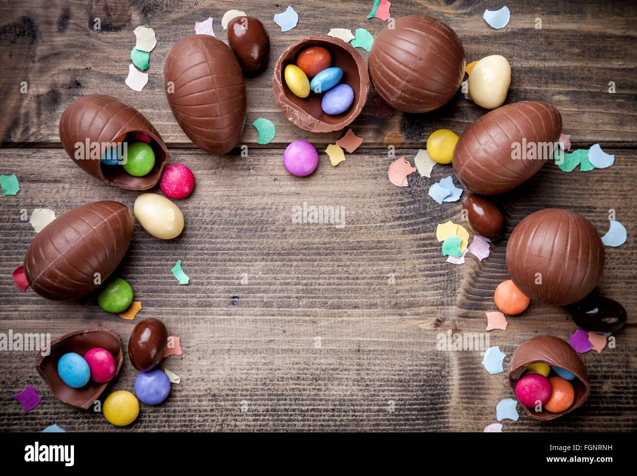 Deliziose uova di pasqua di cioccolato e caramelle su sfondo di legno Immagini Stock
