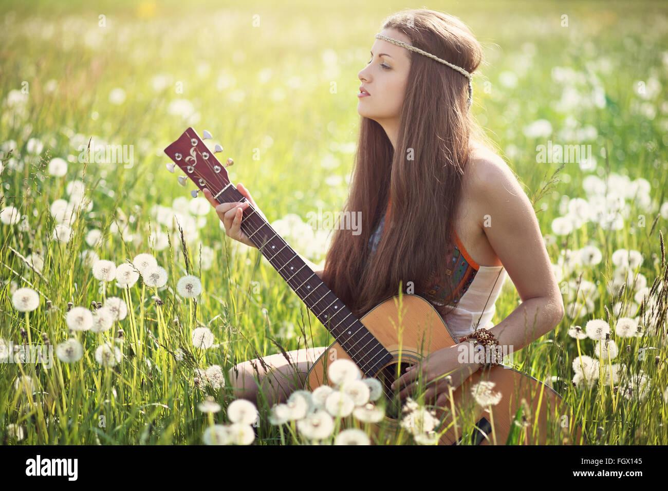 Hippie donna con chitarra in prato estivo . L'armonia della natura Immagini Stock