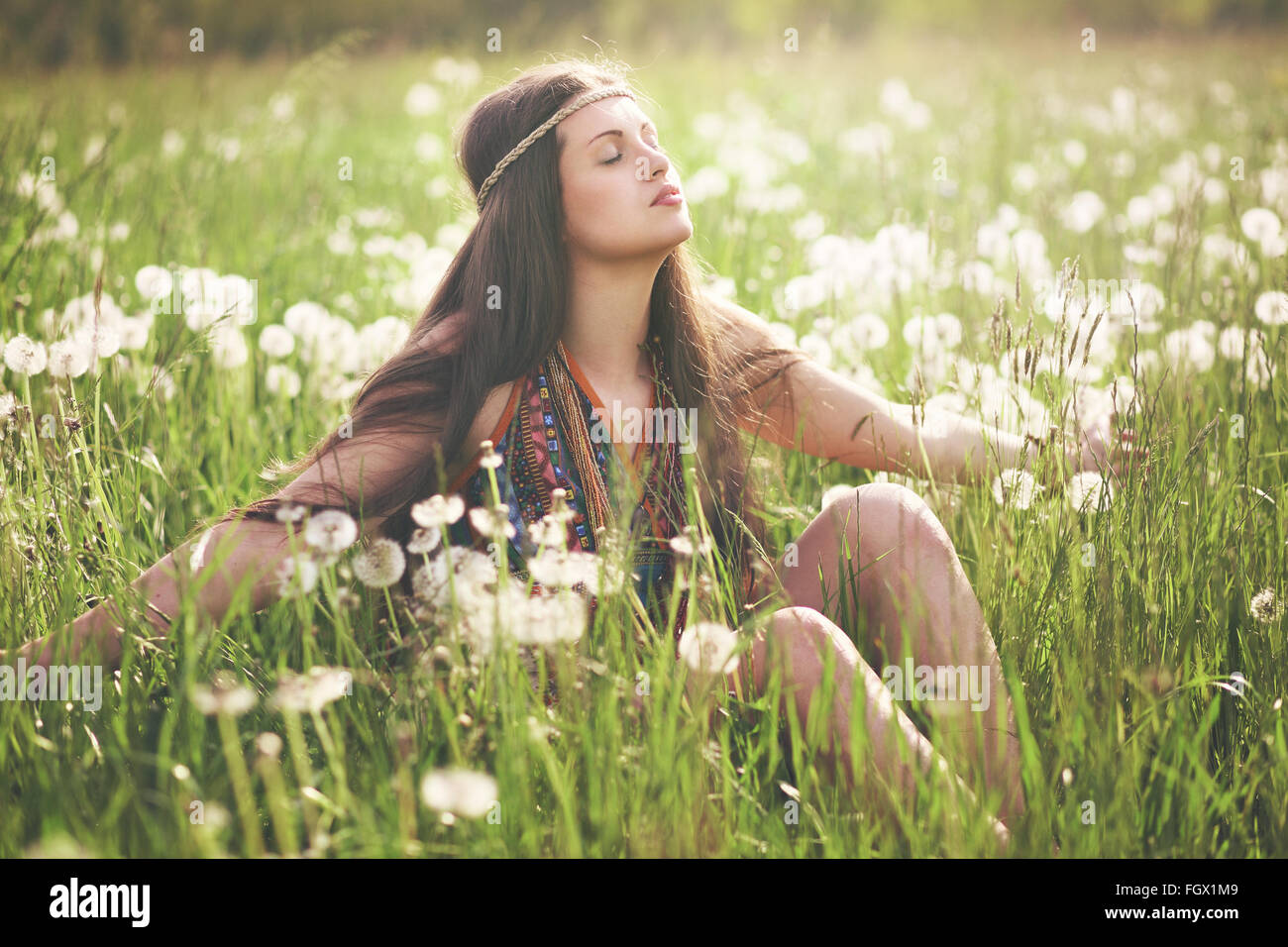 Bella donna hippie godendo della luce del sole in prato fiorito. Armonia con la natura Immagini Stock