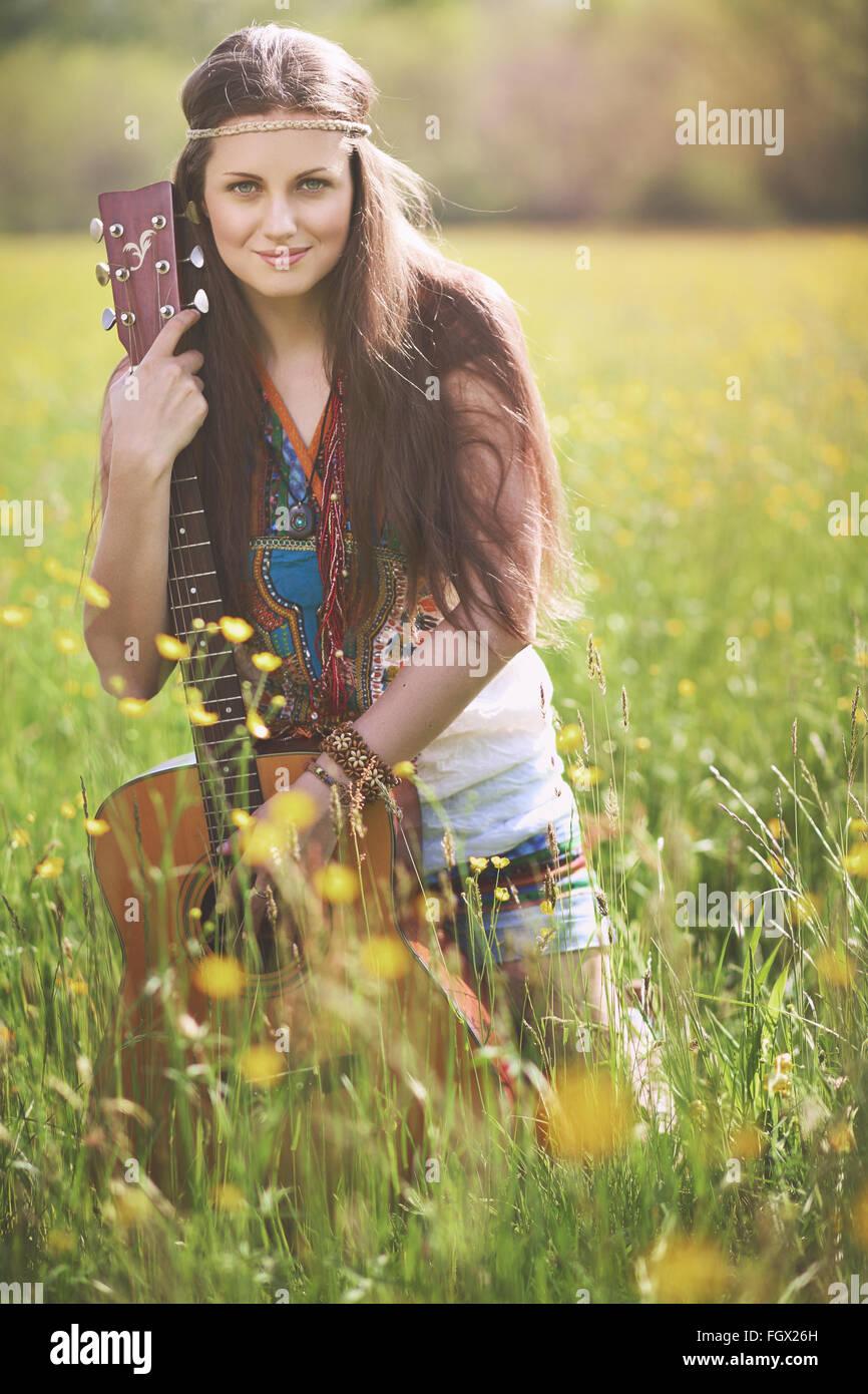 Bella donna hippie in posa con la chitarra . L'armonia della natura Immagini Stock