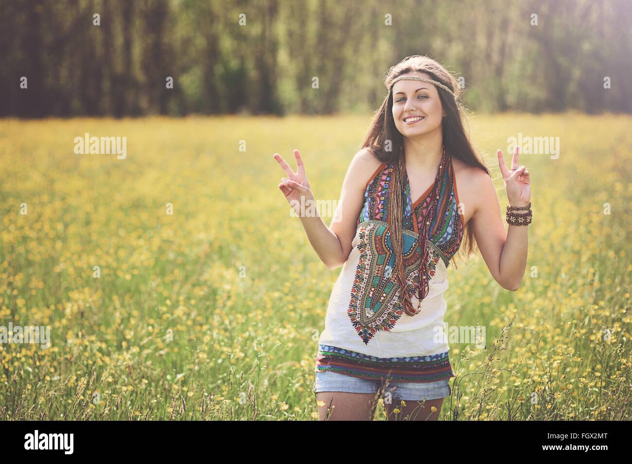 Segno di pace da hippie sorridente in un prato. Libertà e armonia Immagini Stock