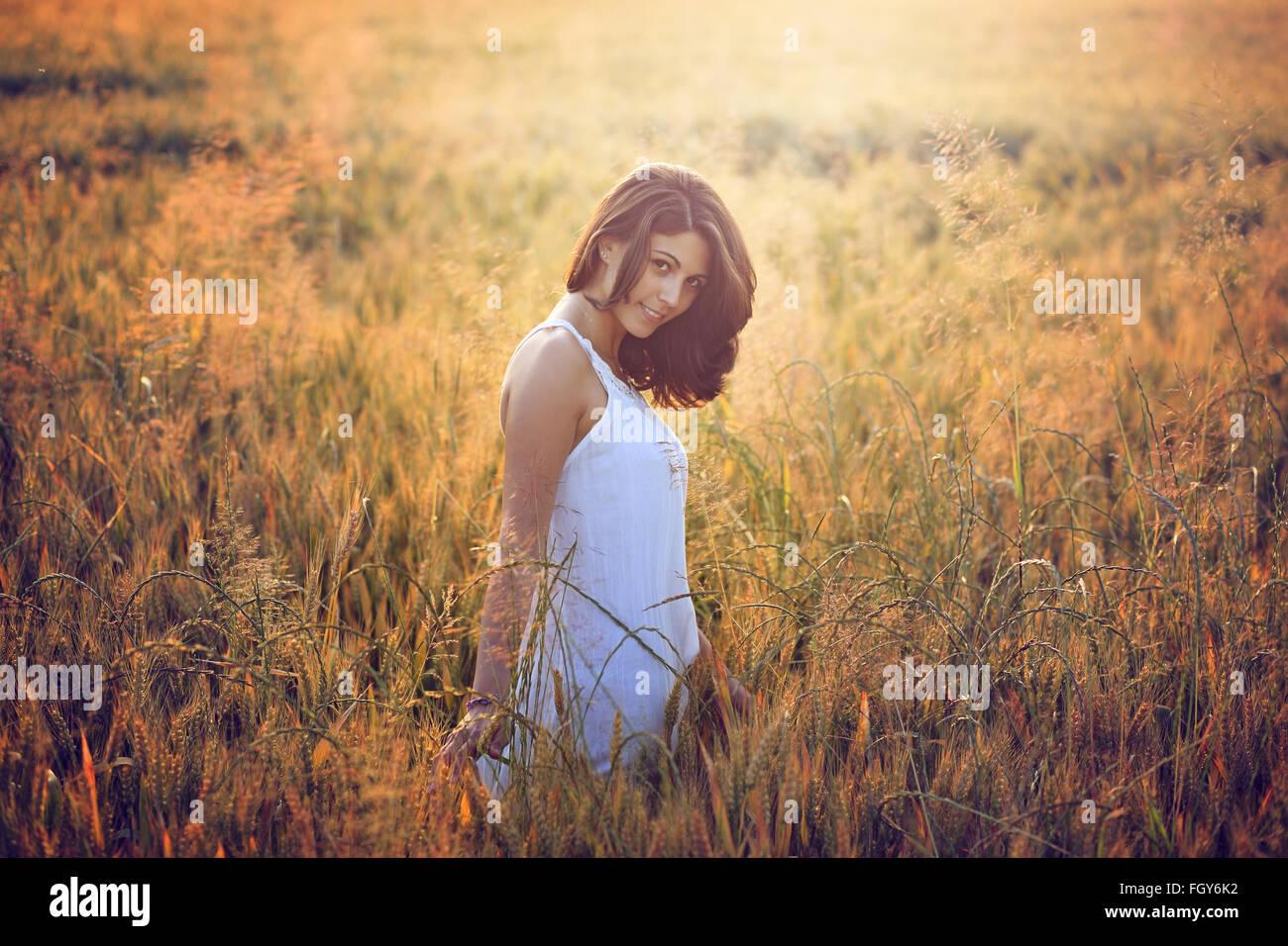 Bella giovane donna in un campo estivo. Calda luce del tramonto ritratto Immagini Stock