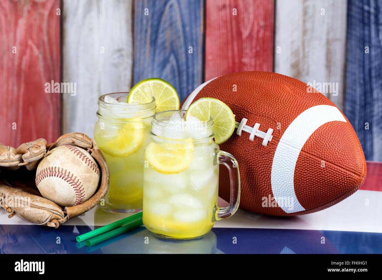 Jar bicchieri riempiti con limonata fredda con articoli sportivi. Sbiadita di tavole di legno dipinte di rosso, Immagini Stock