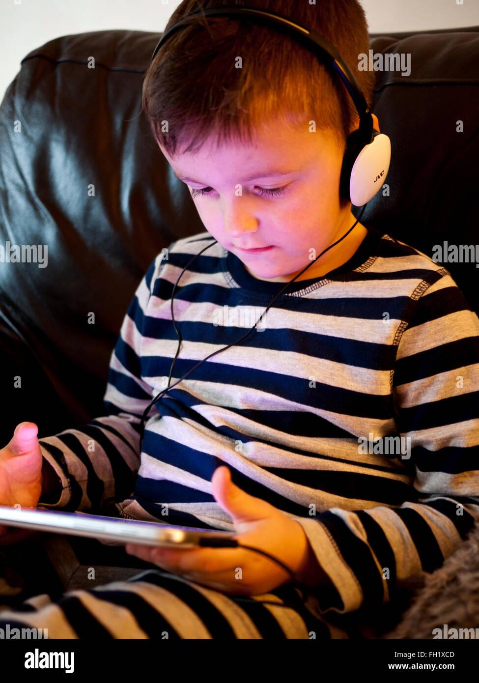 Giovani 5 anno vecchio ragazzo utilizzando un i pad con auricolari, UK. Foto Stock