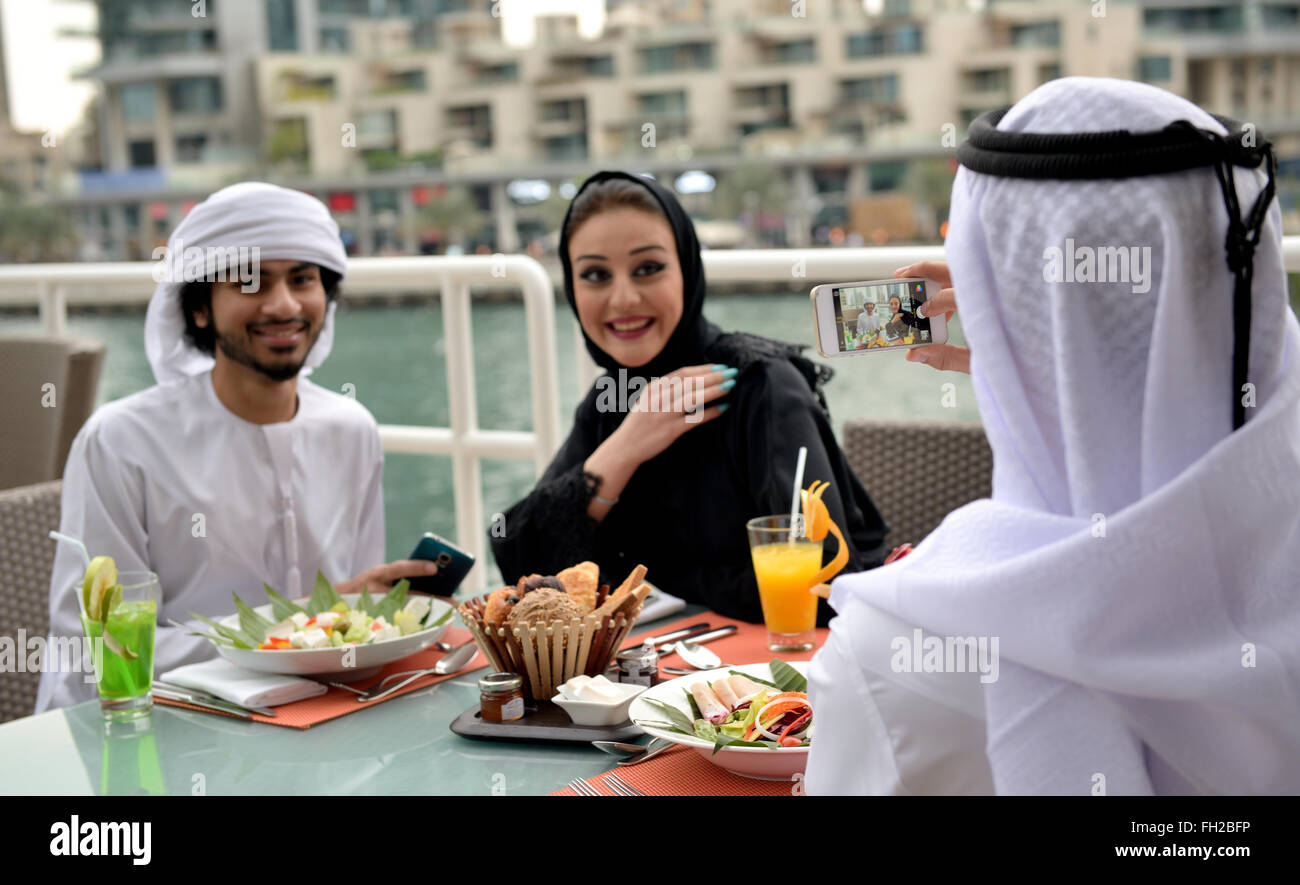 Emirati giovani amici arabi di pranzare in un ristorante Immagini Stock