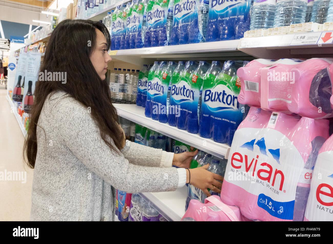 Una giovane donna comprare acqua in bottiglia da scaffale di supermercato Tesco store interno, Suffolk REGNO UNITO Immagini Stock