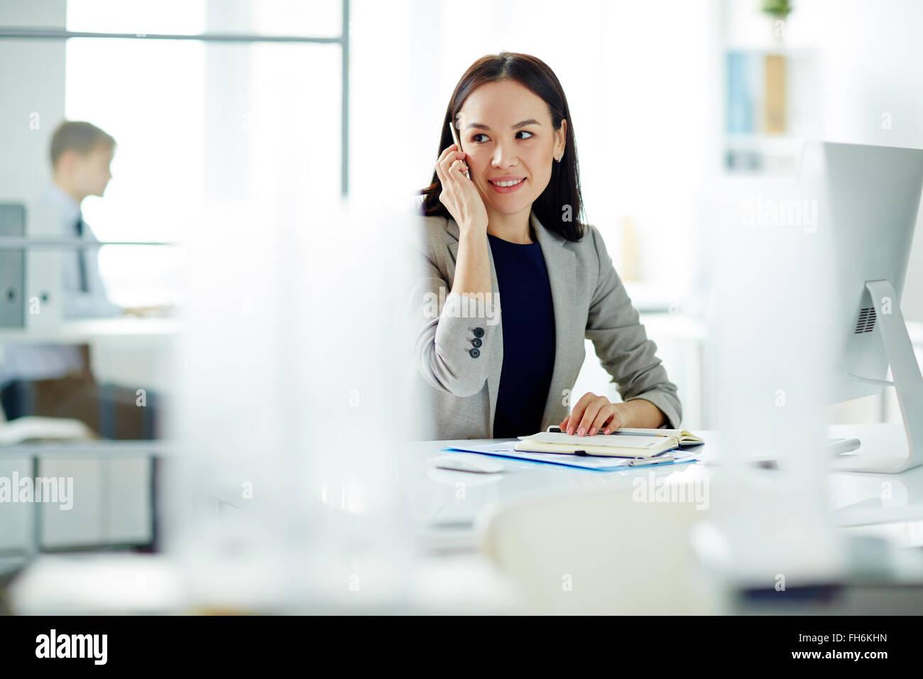 Giovane imprenditrice parlando al telefono mentre i lavori di pianificazione Immagini Stock