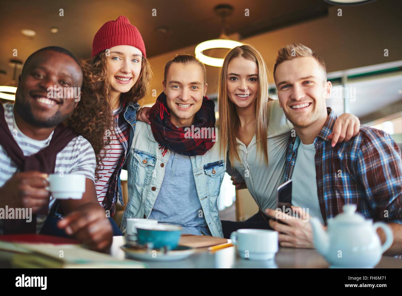Gli adolescenti moderni guardando la telecamera con un sorriso in cafe Immagini Stock