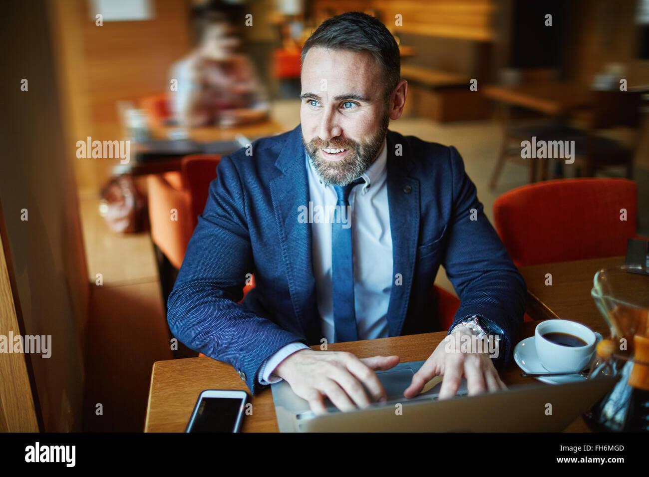 Imprenditore contemporaneo in formale-indossare la digitazione in cafe Immagini Stock
