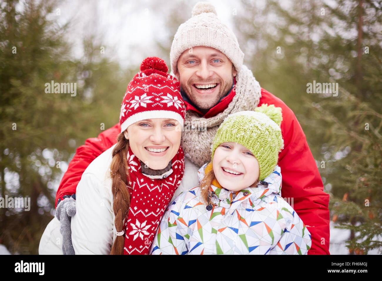 La famiglia felice guardando la fotocamera con toothy sorride all'aperto Immagini Stock