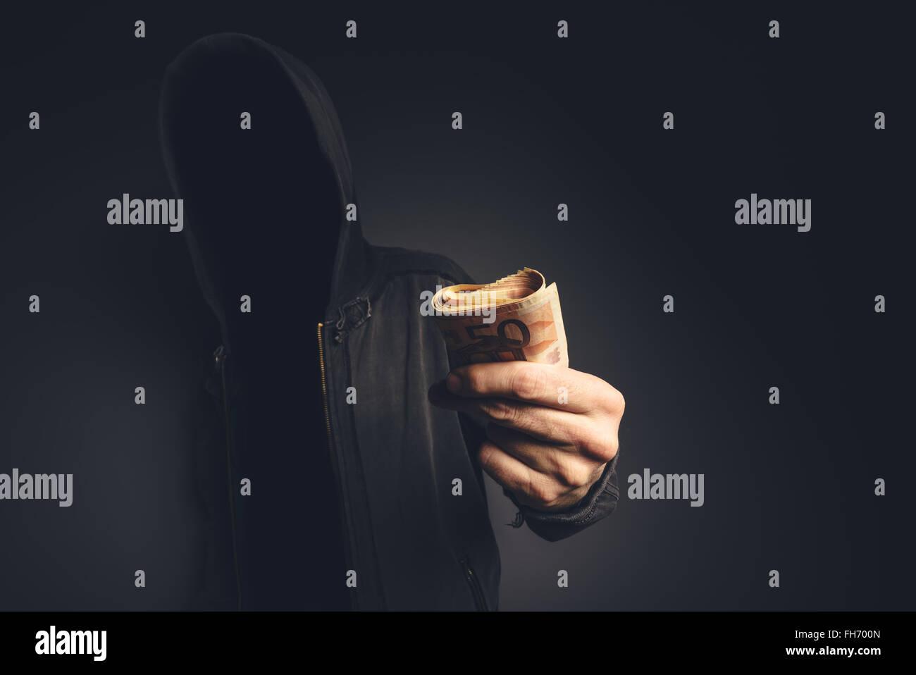 Irriconoscibile incappucciati hacker offrendo denaro contante, cyber criminalità, ricatto e estorsione concetto. Immagini Stock