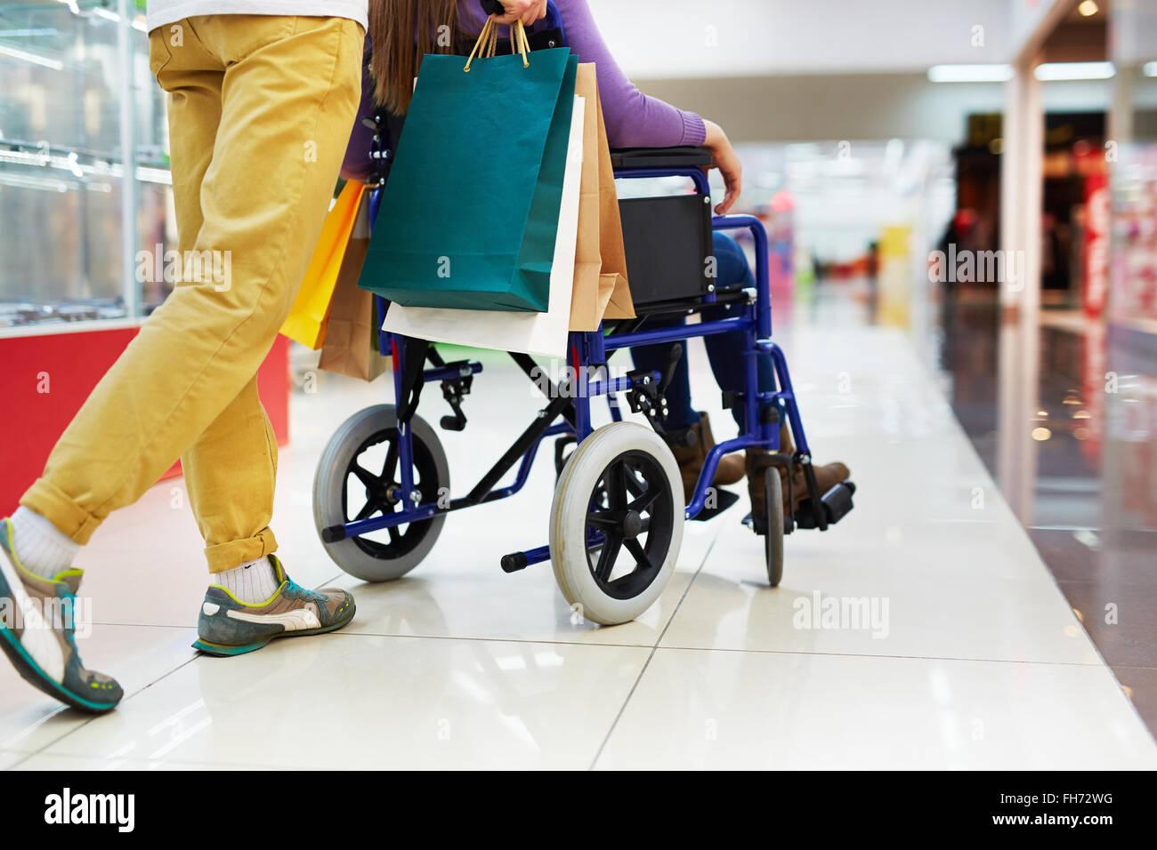 Caring guy aiutare la sua ragazza su una sedia a rotelle con lo shopping Immagini Stock