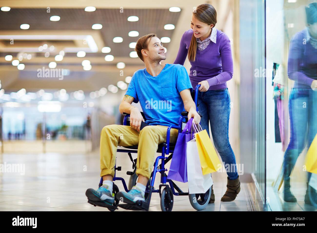 Cura la ragazza a parlare con il suo ragazzo in sedia a rotelle durante la vendita Immagini Stock