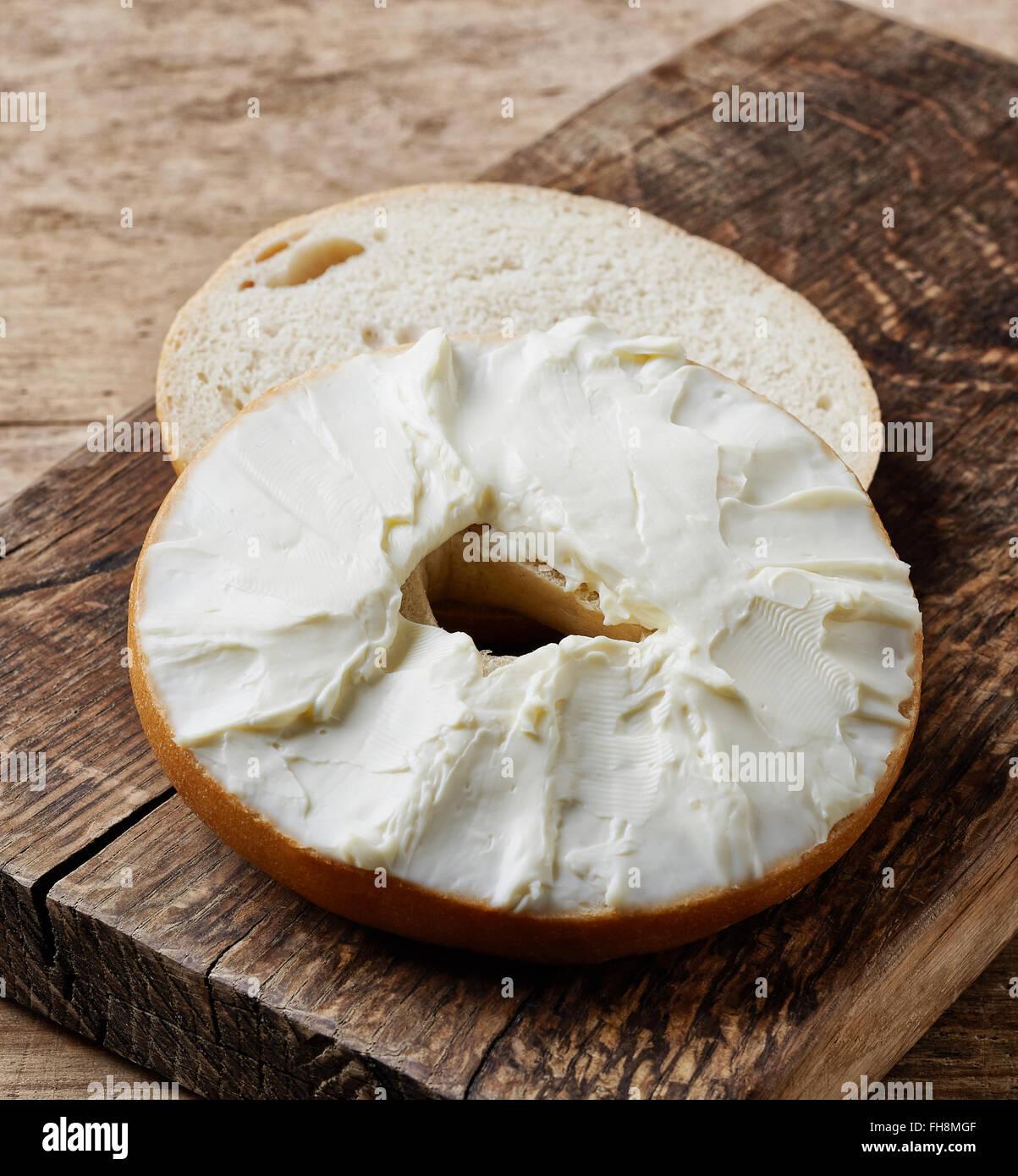 Bagel con formaggio spalmabile su un tavolo di legno Immagini Stock