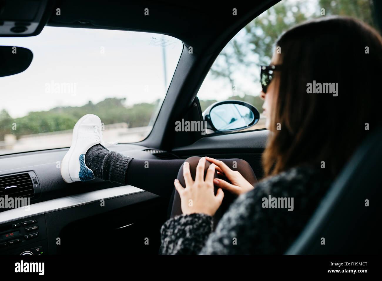 Femmina passeggero anteriore in auto con il piede sul cruscotto Immagini Stock