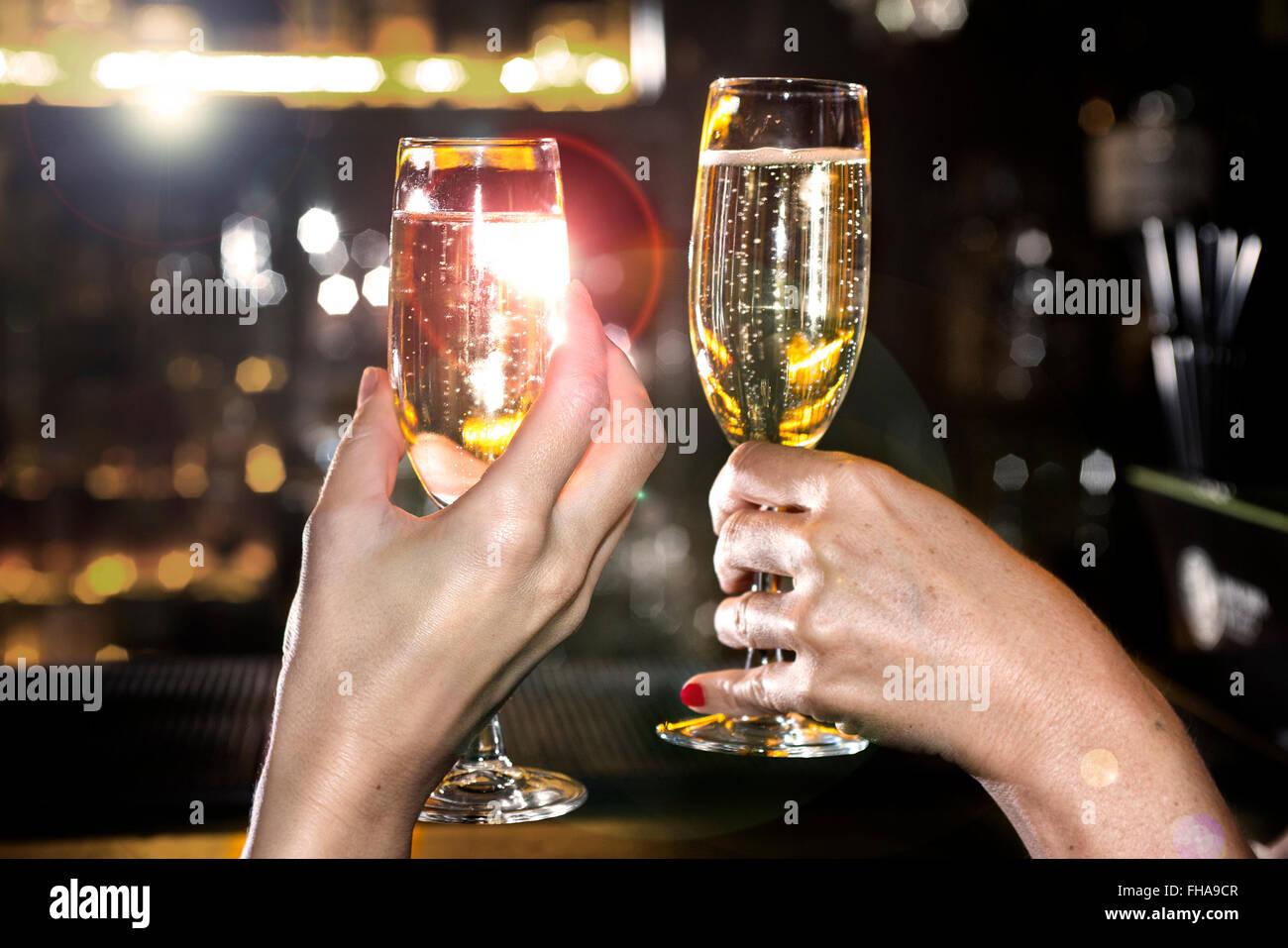 Bere champagne, mani e bicchieri Immagini Stock