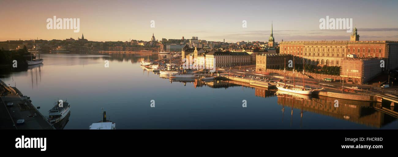 Barche ancorate lungo Skeppsbron all'alba con il Palazzo Reale e la Città Vecchia di Stoccolma Immagini Stock