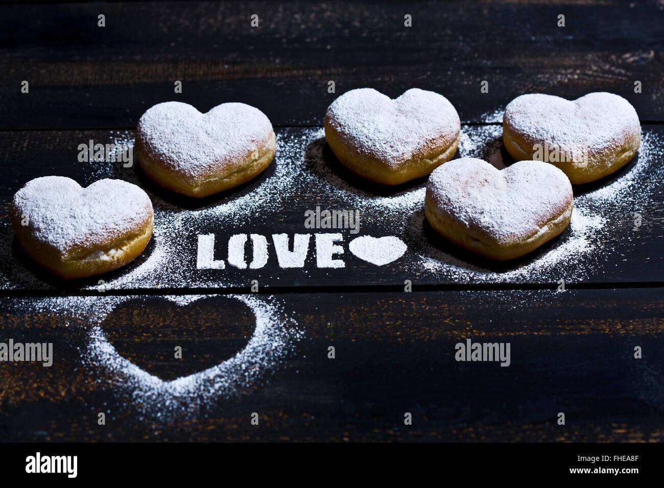 La parola 'amore' stampata con zucchero a velo e 5 a forma di cuore sulla crullers legno scuro Immagini Stock