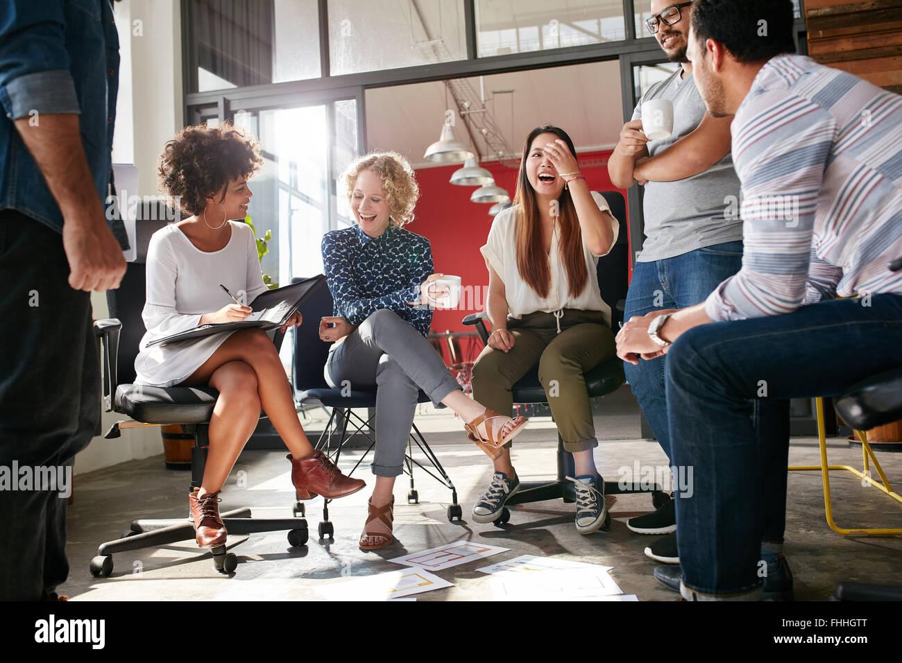 Inquadratura di un gruppo di giovani professionisti di aziende aventi una riunione. Diversi gruppi di giovani designer Foto Stock