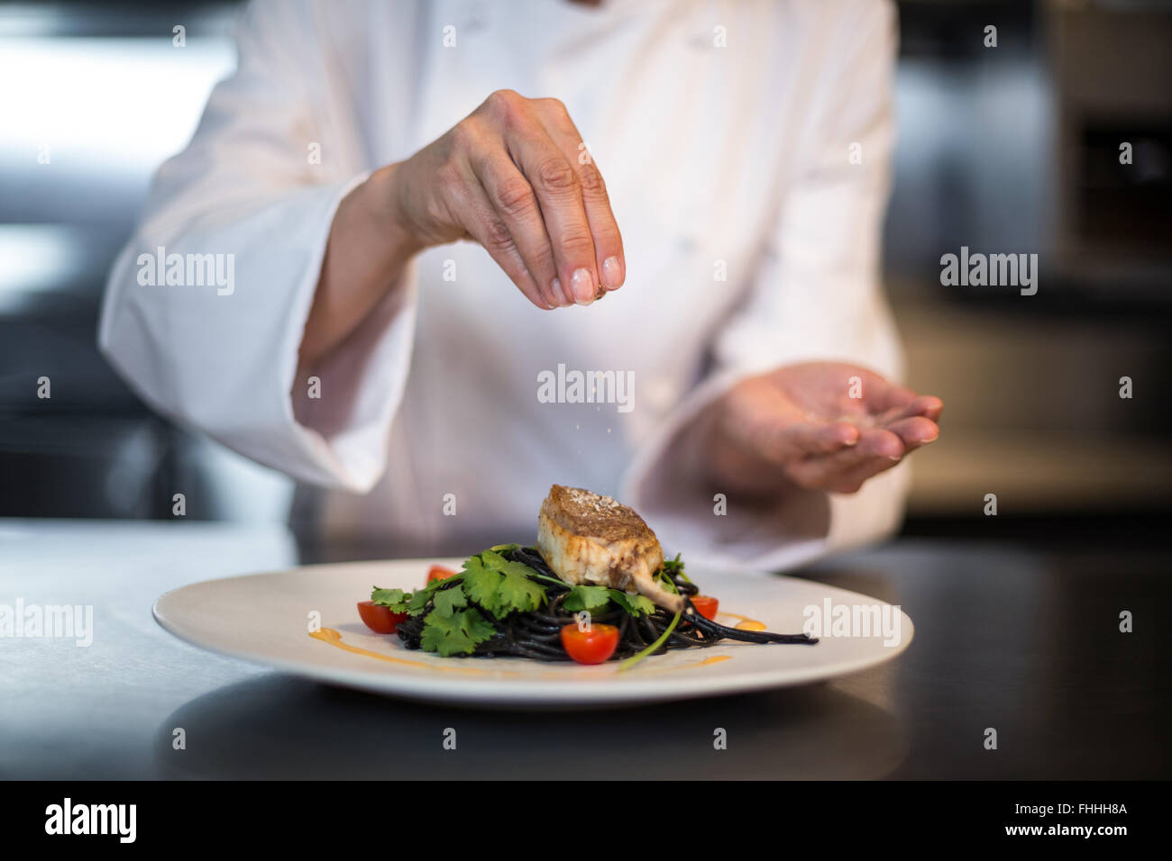Lo Chef condendo il suo piatto Immagini Stock