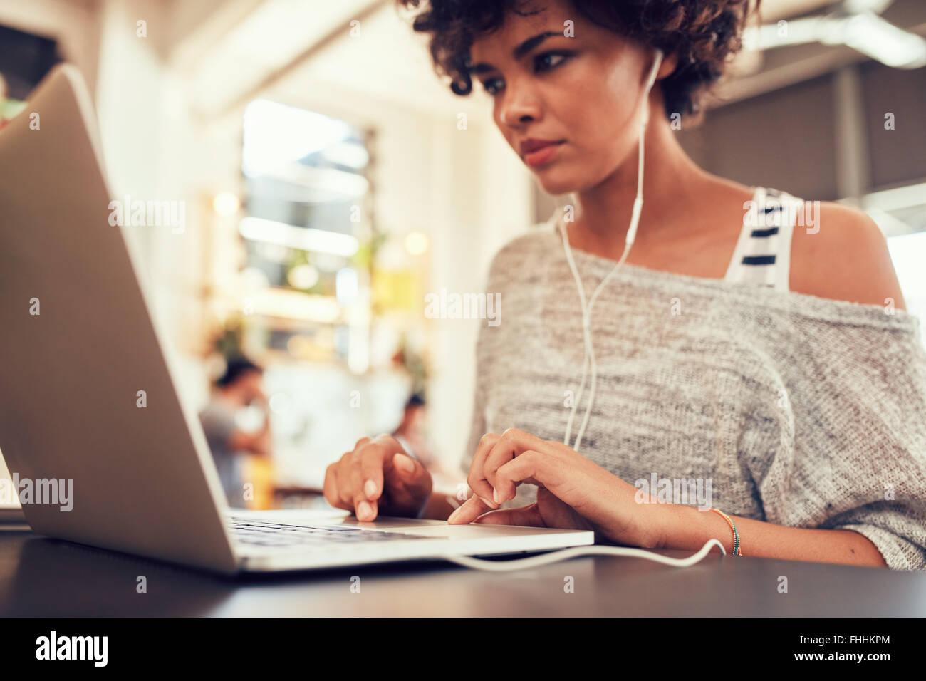 Ritratto di giovane donna alla ricerca occupato a lavorare sul computer portatile in un cafe'. Donna africana in seduta coffee shop utilizzando laptop. Foto Stock