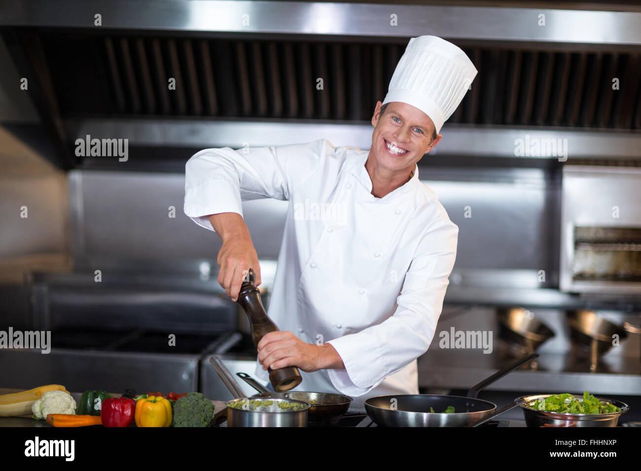 Lo chef felice la stagionatura il suo piatto Immagini Stock