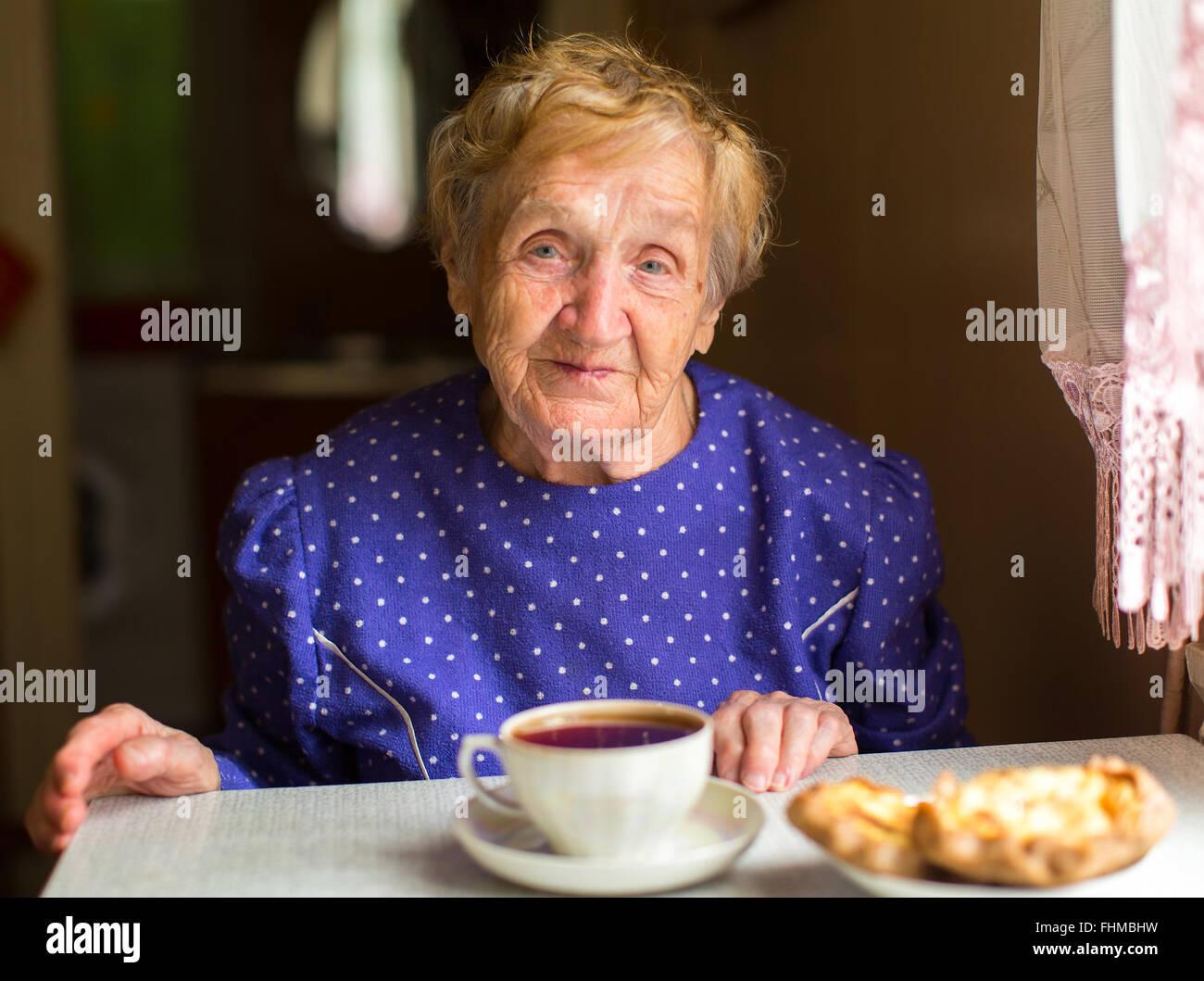 Una donna anziana seduta in cucina a bere il tè. Immagini Stock