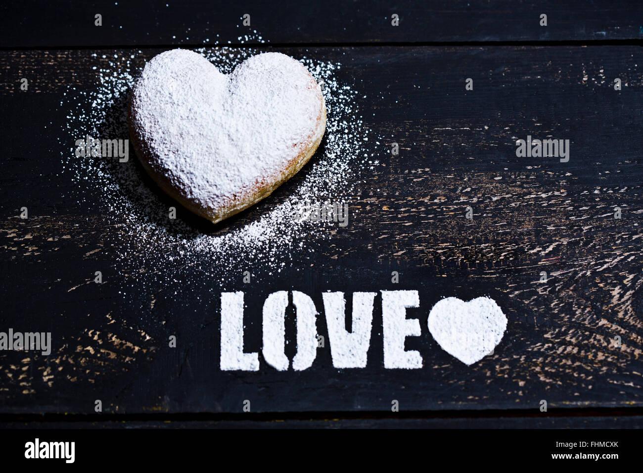 La parola 'amore' stampata con glassa di zucchero e una a forma di cuore sulla cruller legno scuro Immagini Stock