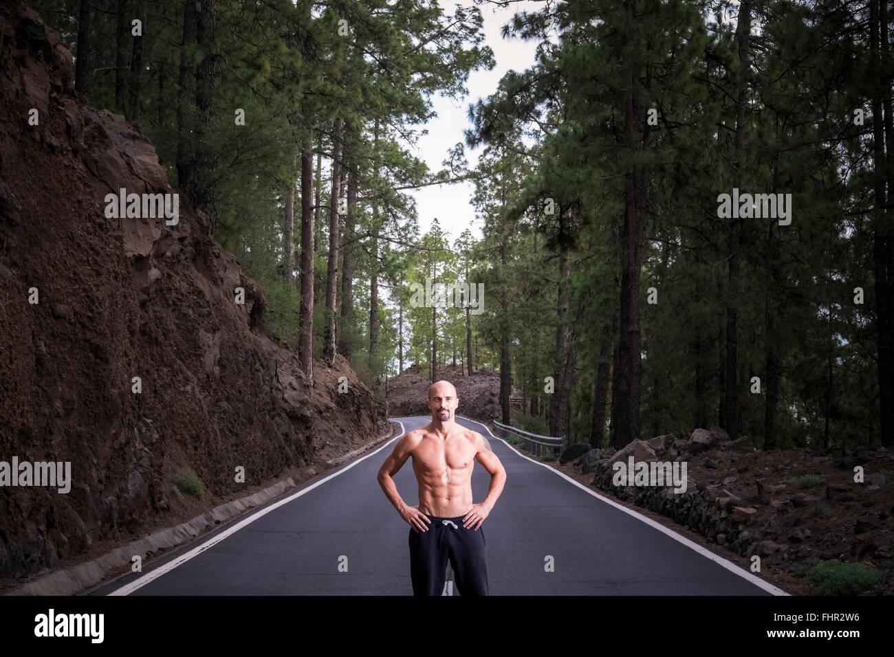 Spagna Tenerife shirtless muscolare uomo con le mani sui suoi fianchi in piedi su una strada vuota Immagini Stock