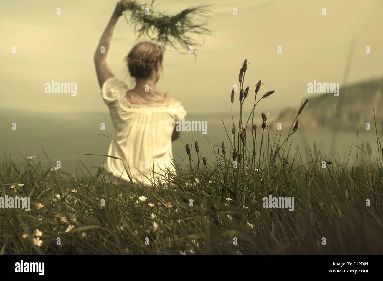 Giovane donna seduta sulla scogliera gesticolando e tenendo l'erba in attesa del suo amante Immagini Stock