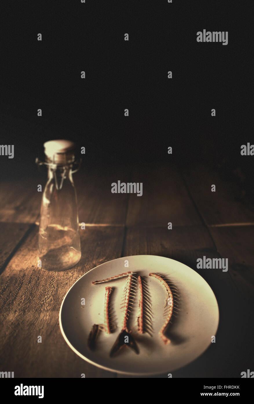 Natura morta con bottiglia di vetro e lische di pesce su di un piatto sul tavolo in legno Immagini Stock