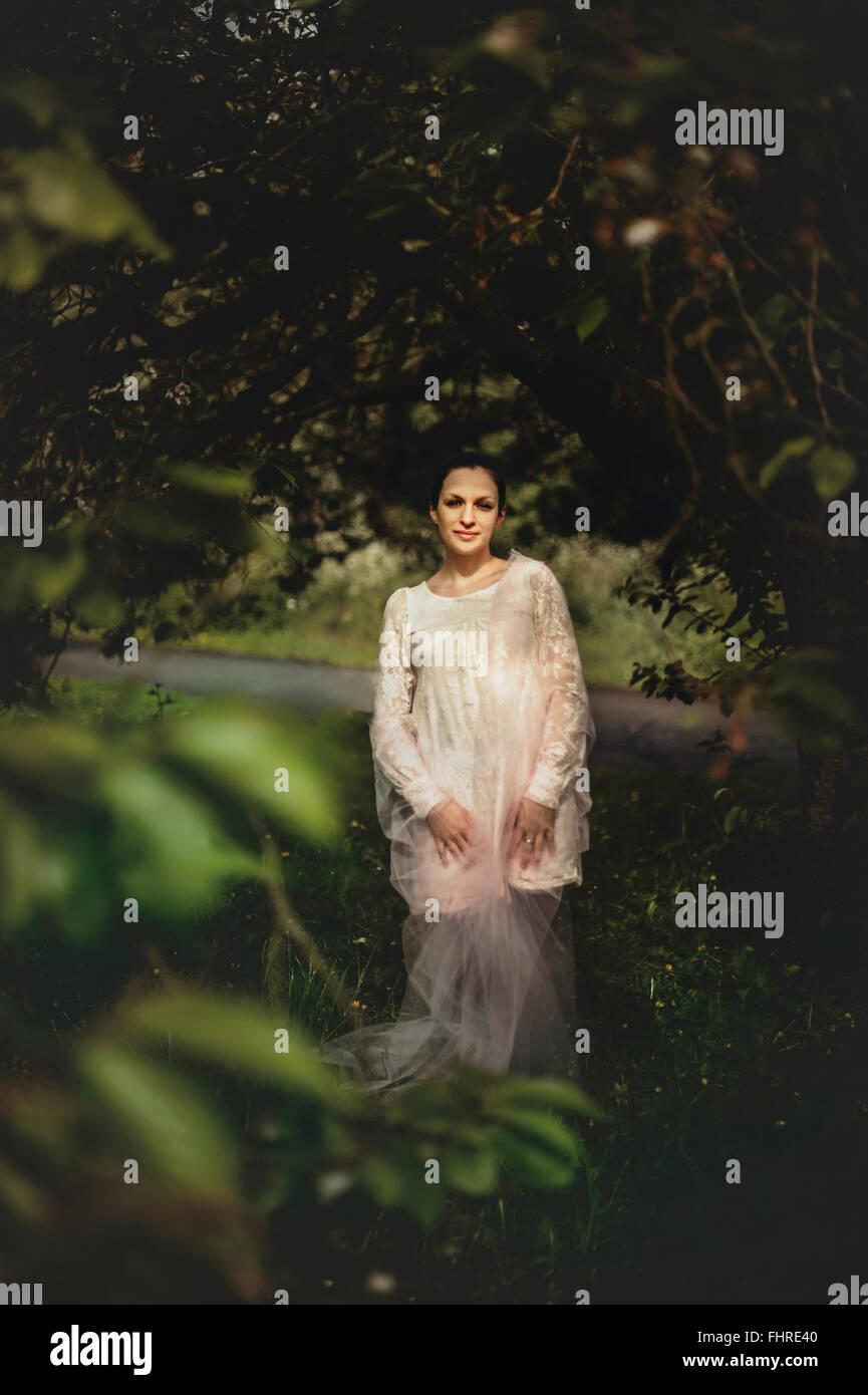 Giovane donna indossa abito bianco in piedi nella foresta Immagini Stock
