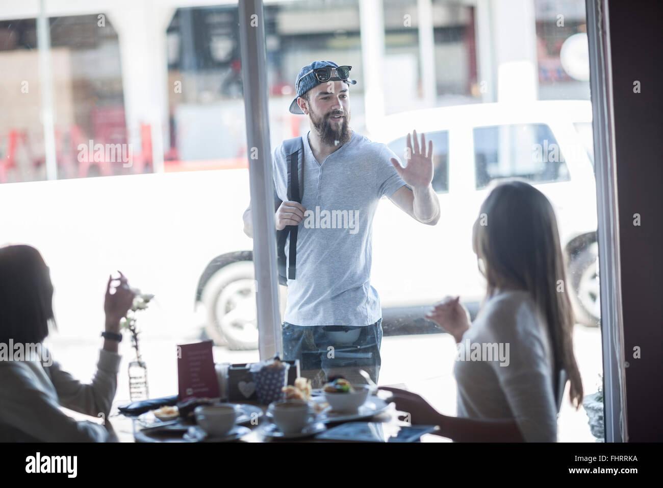 Ritratto di giovane uomo saluto un amico al di fuori di un coffee shop Immagini Stock