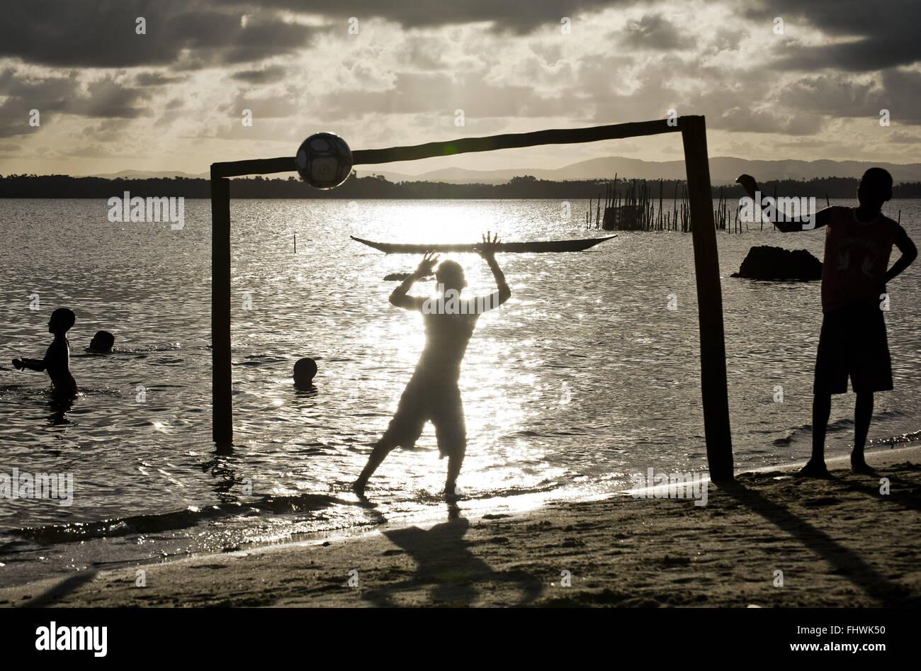Ragazzi giocare a palla sul lungomare di Praia de dentro - Peninsula de Marau Immagini Stock