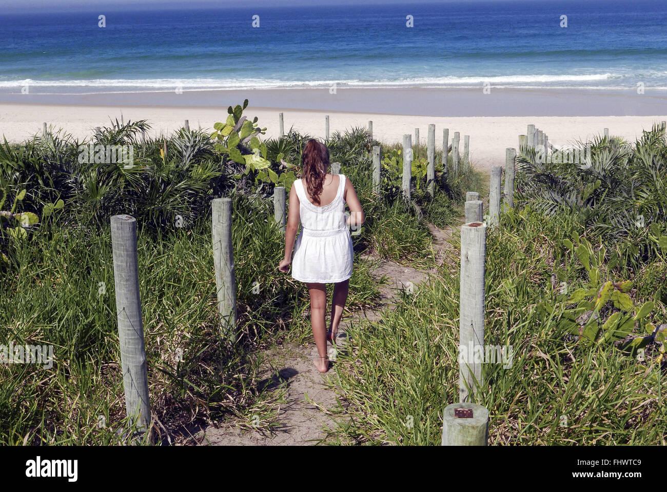 Adolescente caminha pela trilha meio un vegetação de restinga na Praia da Reserva - Barra da Tijuca Immagini Stock