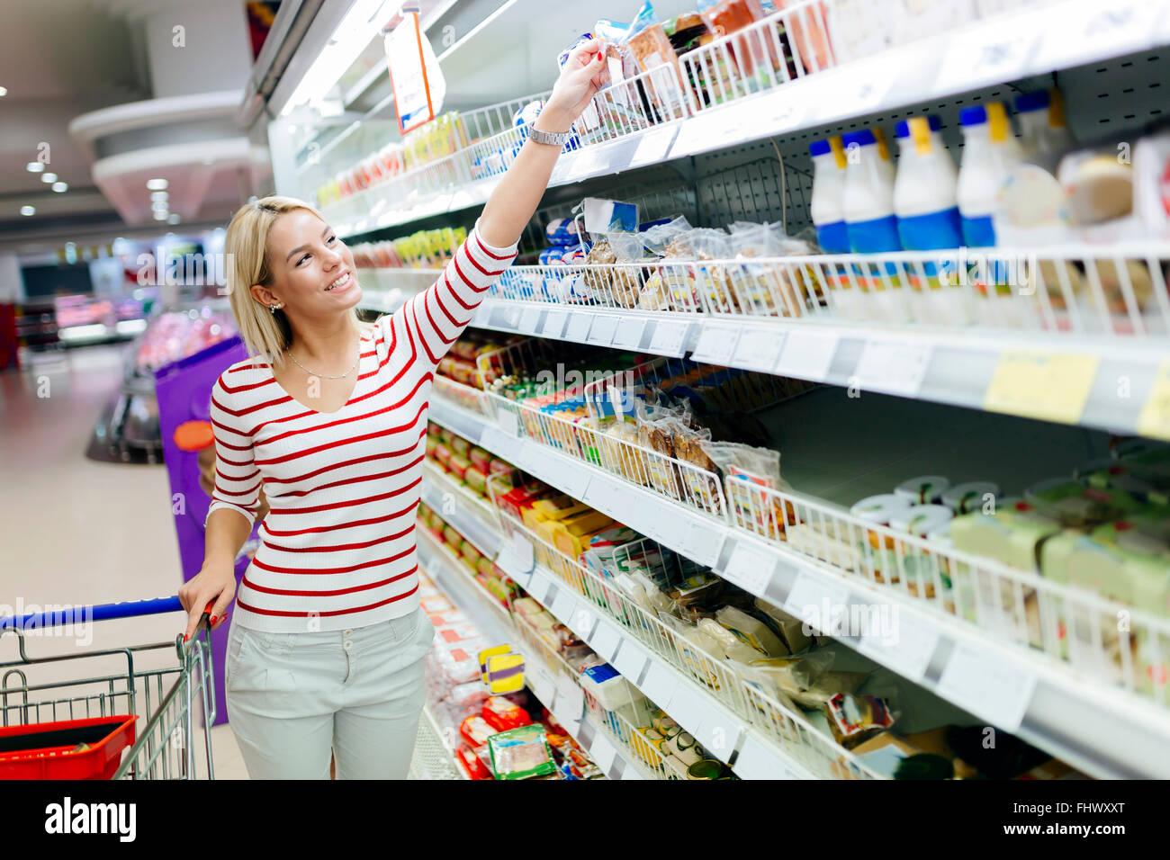 Bella donna shopping nel supermercato e decidere cosa acquistare Immagini Stock