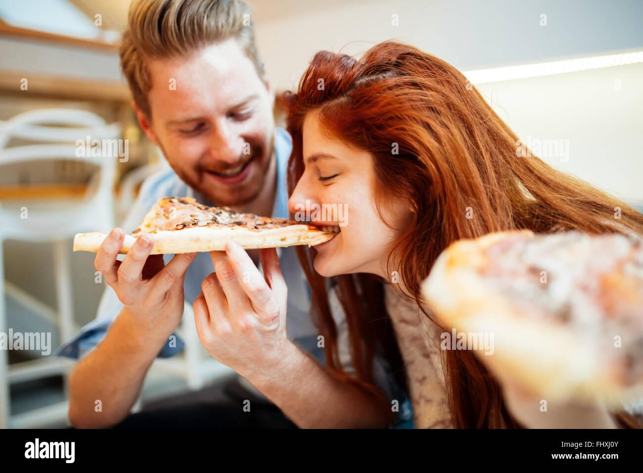 Giovane condividere pizza e mangiare insieme felicemente Immagini Stock