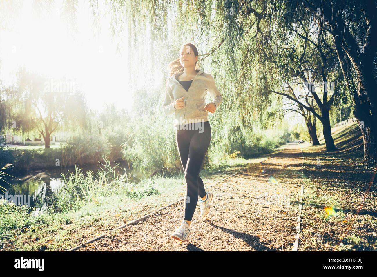 Montare la donna a fare jogging nel parco circondato da alberi Immagini Stock