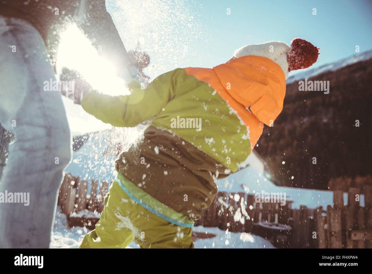 L'Italia, Val Venosta, Slingia, padre e figlio avente una lotta con le palle di neve Foto Stock