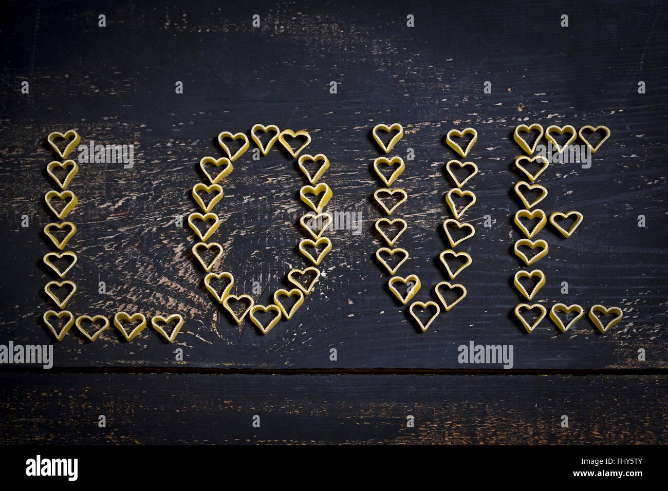 A forma di cuore noodles formante la wotd 'amore' su legno Immagini Stock