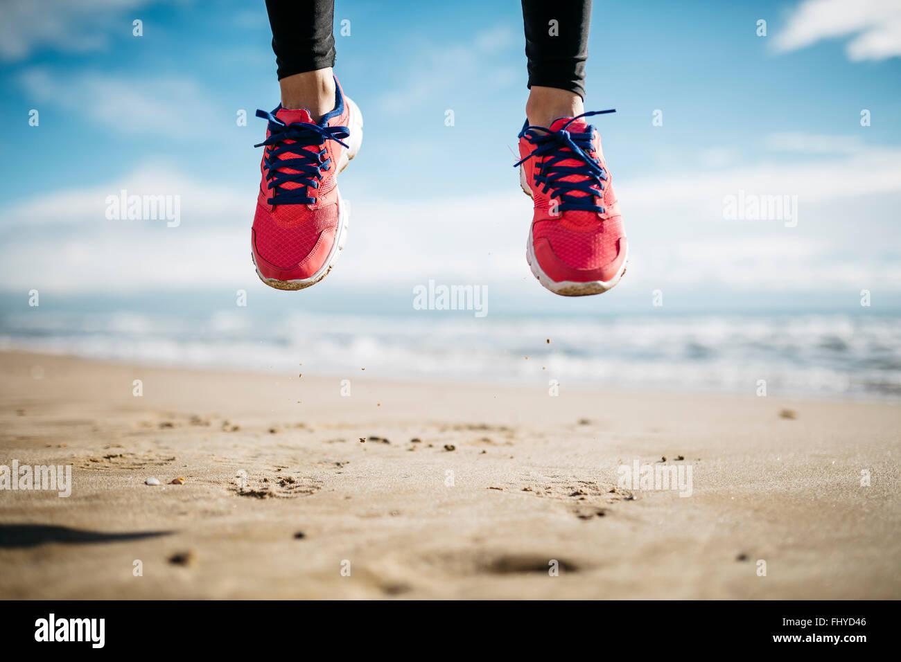Vai a pochi piedi calzati in scarpe da ginnastica, sulla spiaggia Immagini Stock