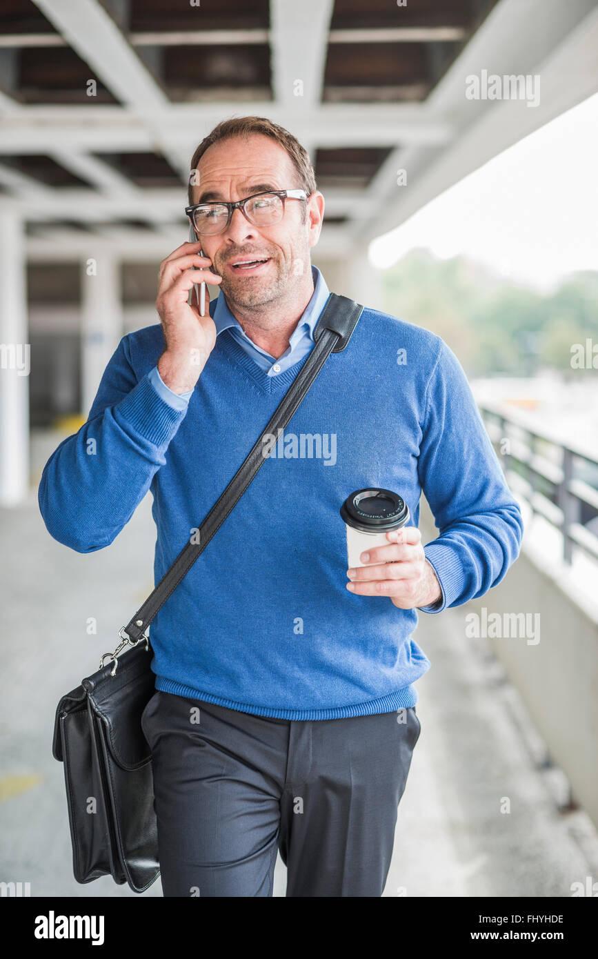 Imprenditore con un telefono cellulare e il caffè per andare in movimento Immagini Stock
