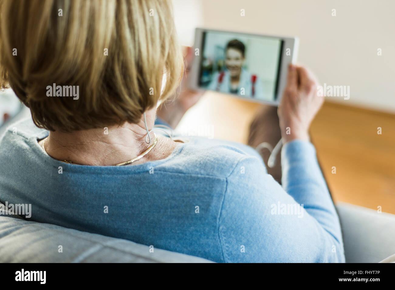 Senior donna che guarda la foto del giovane uomo su tavoletta digitale Foto Stock