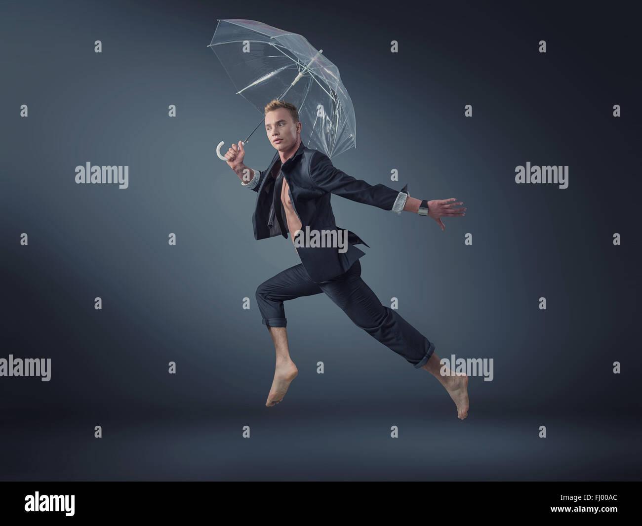 Bello manager jumping con un ombrello trasparente Immagini Stock