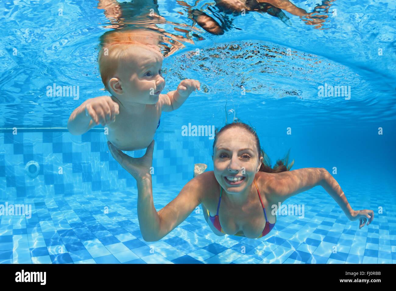 Bambino lezione di nuoto - baby boy con la madre imparare ad immergersi sott'acqua nella piscina con acque blu cristallo. Foto Stock