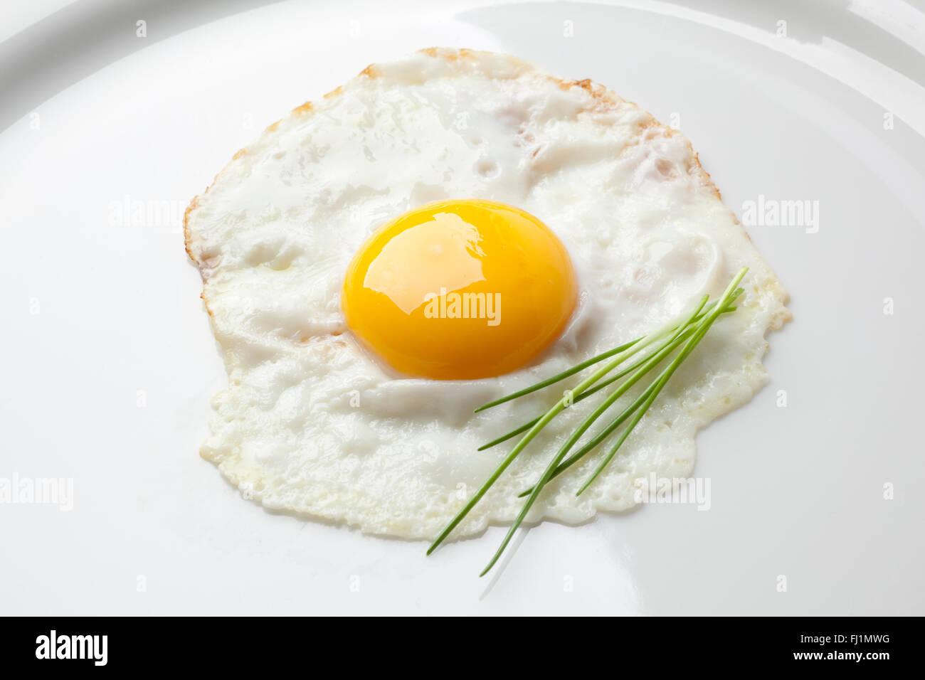 Uovo fritto sunny side up con erba cipollina su una piastra bianca Immagini Stock