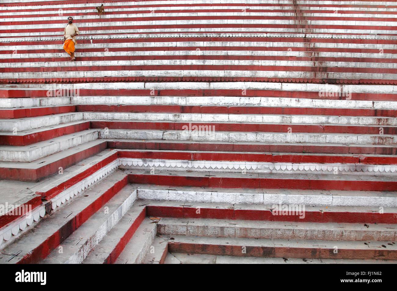 L'uomo cammina da sola con il cane sui gradini di Kedar ghat Varanasi , India Foto Stock